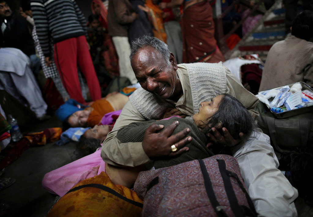 Description of . An Indian man weeps as he holds his wife who was killed in a stampede on a railway platform at the main railway station in Allahabad, India, Sunday, Feb. 10, 2013.   (AP Photo/Kevin Frayer)