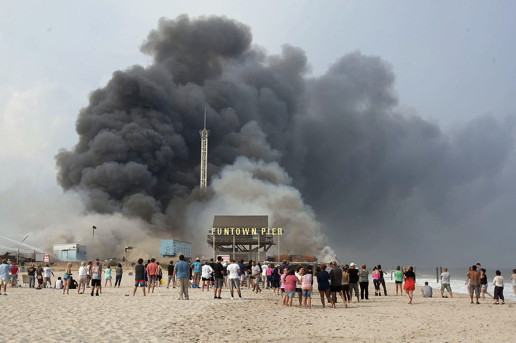 Description of . Onlookers watch from the shore as black smoke rises from a fire on the Seaside Heights, N.J. boardwalk Thursday, Sept. 12, 2013. The fire started in the vicinity of an ice cream shop and burned several blocks of boardwalk and businesses in a town that was still rebuilding from damage caused by Superstorm Sandy. (AP Photo/The Asbury Park Press, Bob Bielk)