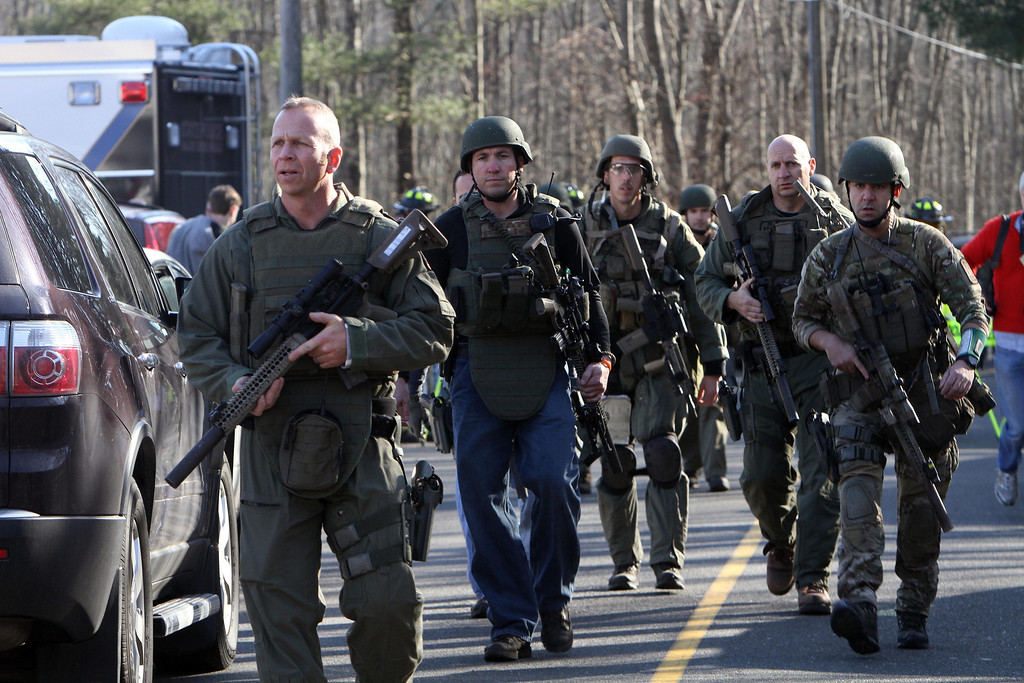 Description of . Heavily armed Connecticut State troopers are on the scene at the Sandy Hook School following a shooting at the school, Friday, Dec. 14, 2012 in Newtown, Conn. A man opened fire inside the Connecticut elementary school where his mother worked Friday, killing 26 people, including 18 children, and forcing students to cower in classrooms and then flee with the help of teachers and police. (AP Photo/The Journal News, Frank Becerra Jr.)