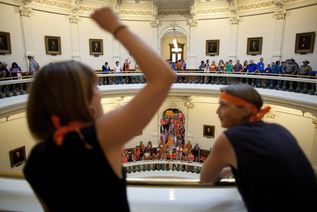 Description of . Hallie Boas and Lisa Fithian lead abortion rights chants from the third floor of the Texas Capitol Rotunda in Austin, Texas on Friday, July 12, 2013. The Texas Senate's leader, Lt. Gov. David Dewhurst, has scheduled a vote for Friday on the same restrictions on when, where and how women may obtain abortions in Texas that failed to become law after a Democratic filibuster and raucous protesters were able to run out the clock on an earlier special session. (AP Photo/Tamir Kalifa)