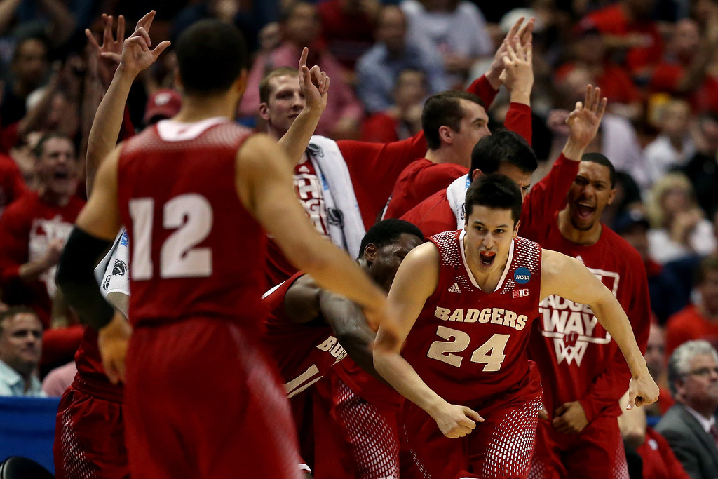 Description of . Bronson Koenig #24 of the Wisconsin Badgers celebrates after making a three-pointer in the second half while taking on the Arizona Wildcats during the West Regional Final of the 2014 NCAA Men's Basketball Tournament at the Honda Center on March 29, 2014 in Anaheim, California.  (Photo by Jeff Gross/Getty Images)