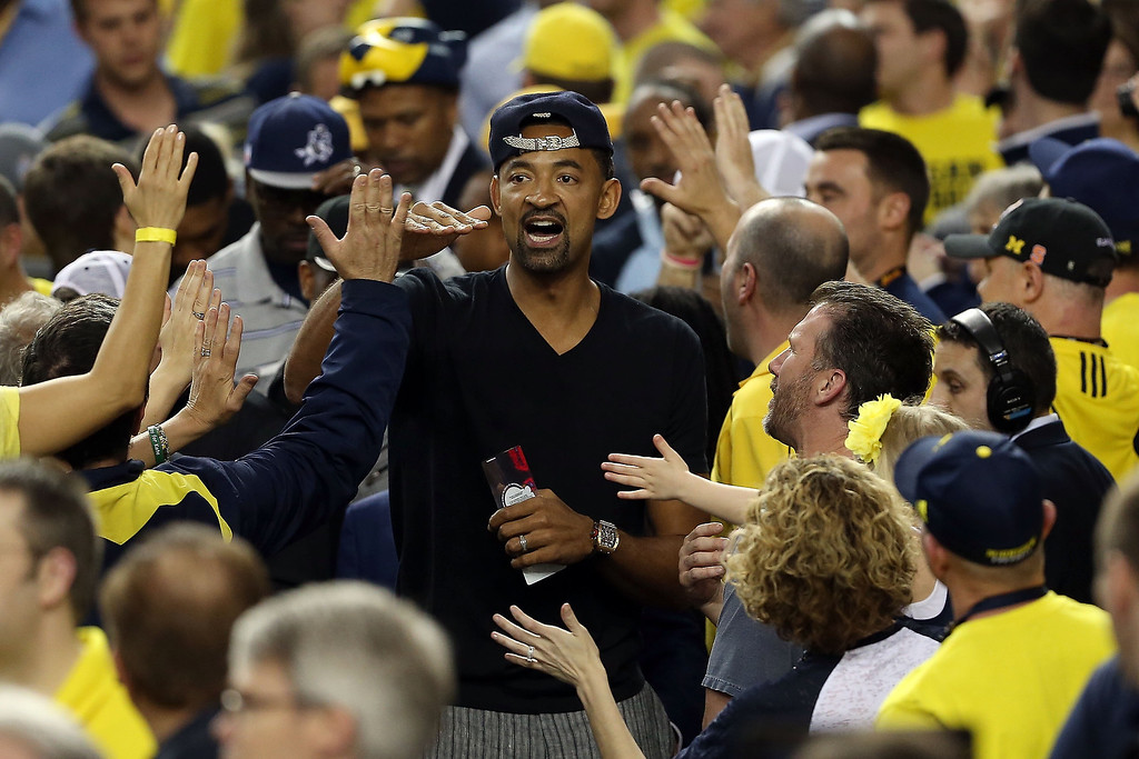 Description of . Former Michigan Wolverines player Juwan Howard greets Michigan fans in the stands against the Louisville Cardinals during the 2013 NCAA Men's Final Four Championship at the Georgia Dome on April 8, 2013 in Atlanta, Georgia.  (Photo by Andy Lyons/Getty Images)