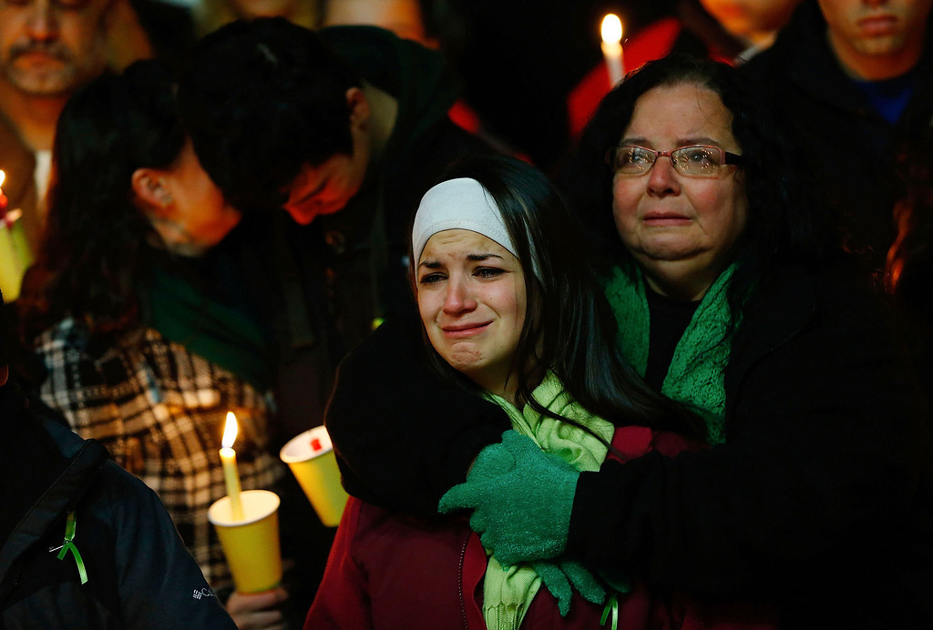 Description of . Donna Soto (R), mother of Victoria Soto, the first-grade teacher at Sandy Hook Elementary School who was shot and killed while protecting her students, hugs her daughter Karly (second from right) while mourning their loss with Victoria's other two siblings, Jillian (far left) and Matthew Soto (second from left), at a candlelight vigil at Stratford High School on December 15, 2012 in Stratford, Connecticut. Twenty-six people were shot dead, including twenty children, after a gunman identified as Adam Lanza opened fire in the school. Lanza also reportedly had committed suicide at the scene. A 28th person, believed to be Nancy Lanza was found dead in a house in town, was also believed to have been shot by Adam Lanza. (Photo by Jared Wickerham/Getty Images)