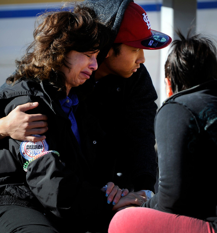 Description of . A women is consoled by a young man at the scene of shooting at 16005 Ithaca Place in Aurora Saturday afternoon. The bodies of four people, including a gunman are dead at the scene following a standoff situation early Saturday morning. The Denver Post/ Andy Cross