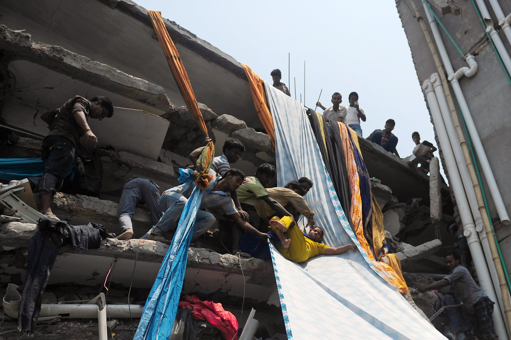 Description of . Bangladeshi garment workers assist a survivor onto a length of textile to be used as an evacuation slide after an eight-story building collapsed in Savar, on the outskirts of Dhaka, on April 24, 2013.   AFP PHOTO/Munir uz ZAMAN/AFP/Getty Images