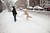 A woman plays with her dog in the snow in the Prospect Heights section on March 8, 2012 in Brooklyn borough of New York City. The storm part of the same system that pummeled the Midwest is expected to dump one to two inches of snow in the New York Metro area.  (Photo by Ramin Talaie/Getty Images)