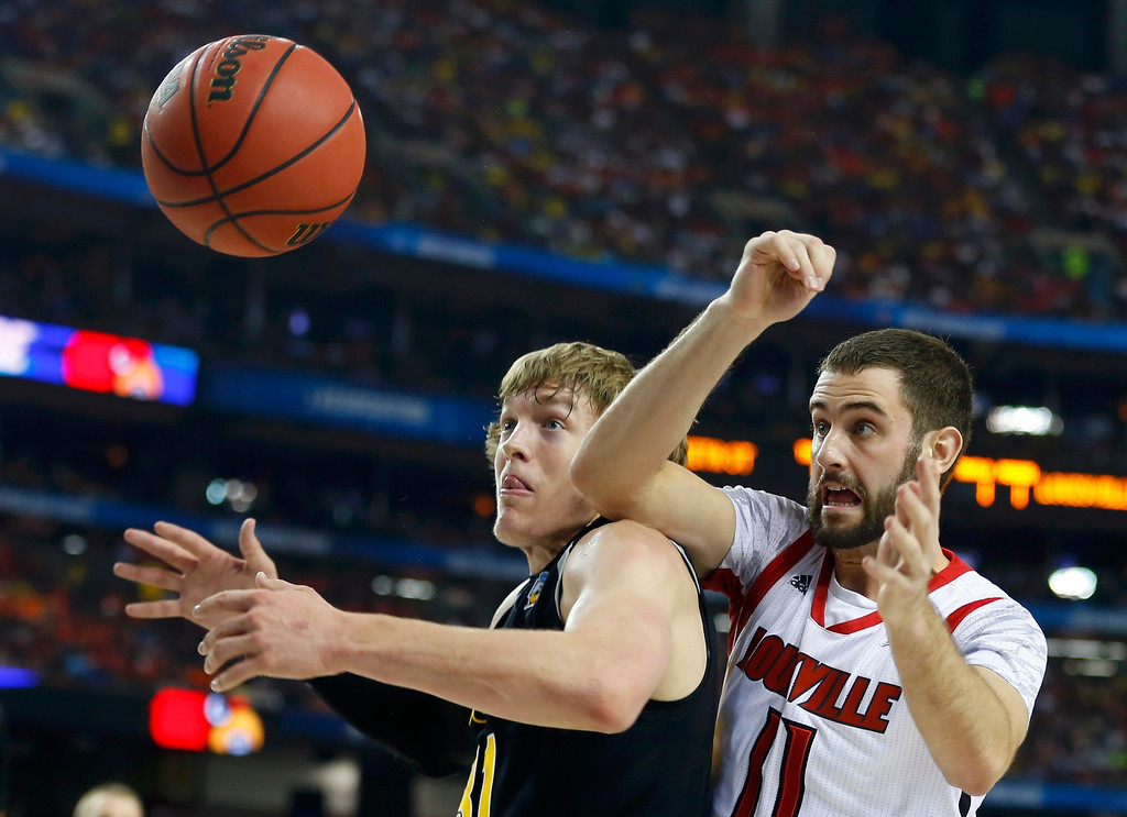 Description of . Wichita State Shockers guard Ron Baker (L) and Louisville Cardinals guard/forward Luke Hancock battle for the ball during the first half of their NCAA men's Final Four basketball game in Atlanta, Georgia April 6, 2013. REUTERS/Jeff Haynes