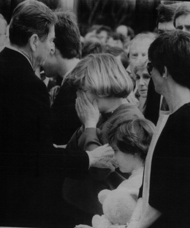 Description of . President Reagan comforts Alison Smith, the daughter of mission 51-L pilot Michael Smith at Friday's memorial service in Houston for the challenger astronauts killed Tuesday in the post-launch explosion. Beside Alison is her sister, Erin.  Denver Post Library Archive