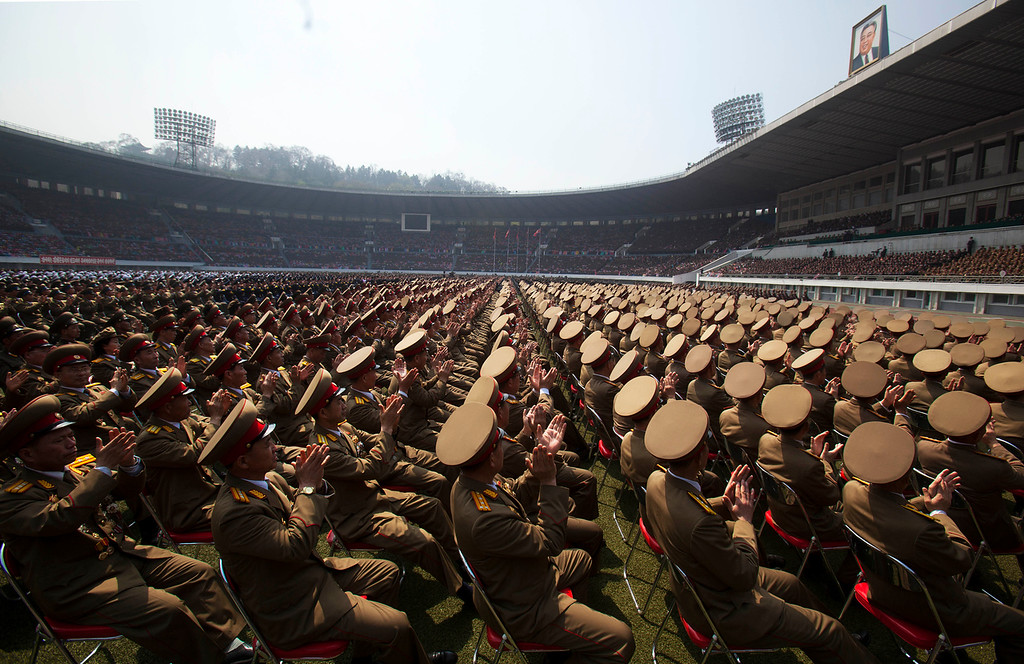 Description of . A crowd of North Korean military members look up to a stadium podium and applaud the country's leader Kim Jong Un and senior military and government officials during a meeting of the Central Committee of North Korea's ruling party in Pyongyang on Saturday April 14, 2012. North Korea will mark the 100-year birth anniversary of the late leader Kim Il Sung on Sunday April 15. (AP Photo/David Guttenfelder)