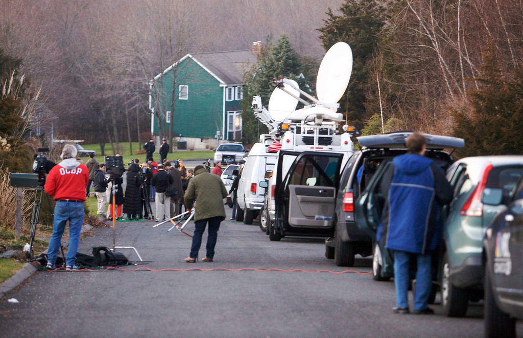 Description of . Members of the media interview neighbours near the secondary crime scene following a shooting at Sandy Hook Elementary School, in Sandy Hook, Connecticut, December 14, 2012. The peace and security of the suburban Connecticut community of Newtown lay shattered on Friday after a gunman attacked a primary school in one of the worst mass shootings in U.S. History. Tearful parents and children gathered around Sandy Hook Elementary School by midday on Friday, surrounded by police vehicles, as young and old alike struggled to make sense of a shooting rampage that killed at least 28 people, including 20 children. REUTERS/Michelle McLoughlin