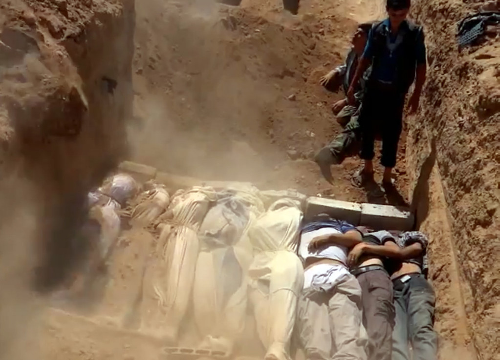 Description of . An image grab taken from a video uploaded on YouTube by the Local Committee of Arbeen on August 21, 2013 allegedly shows Syrians covering a mass grave containing bodies of victims that Syrian rebels claim were killed in a toxic gas attack by pro-government forces in eastern Ghouta and Zamalka, on the outskirts of Damascus. The allegation of chemical weapons being used in the heavily-populated areas came on the second day of a mission to Syria by UN inspectors, but the claim, which could not be independently verified, was vehemently denied by the Syrian authorities, who said it was intended to hinder the mission of UN chemical weapons inspectors. AFP PHOTO / YOUTUBE / LOCAL COMMITTEE OF ARBEEN DSK/AFP/Getty Images