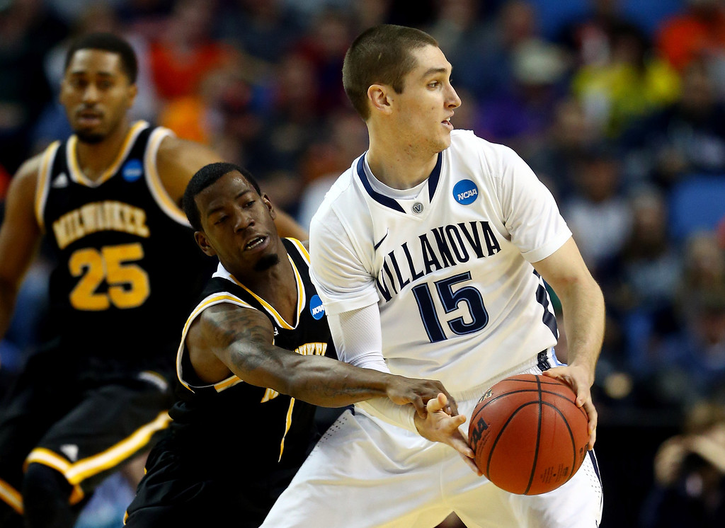 Description of . BUFFALO, NY - MARCH 20: Ryan Arcidiacono #15 of the Villanova Wildcats looks to pass as Jordan Aaron #1 of the Milwaukee Panthers defends during the second round of the 2014 NCAA Men's Basketball Tournament at the First Niagara Center on March 20, 2014 in Buffalo, New York.  (Photo by Elsa/Getty Images)