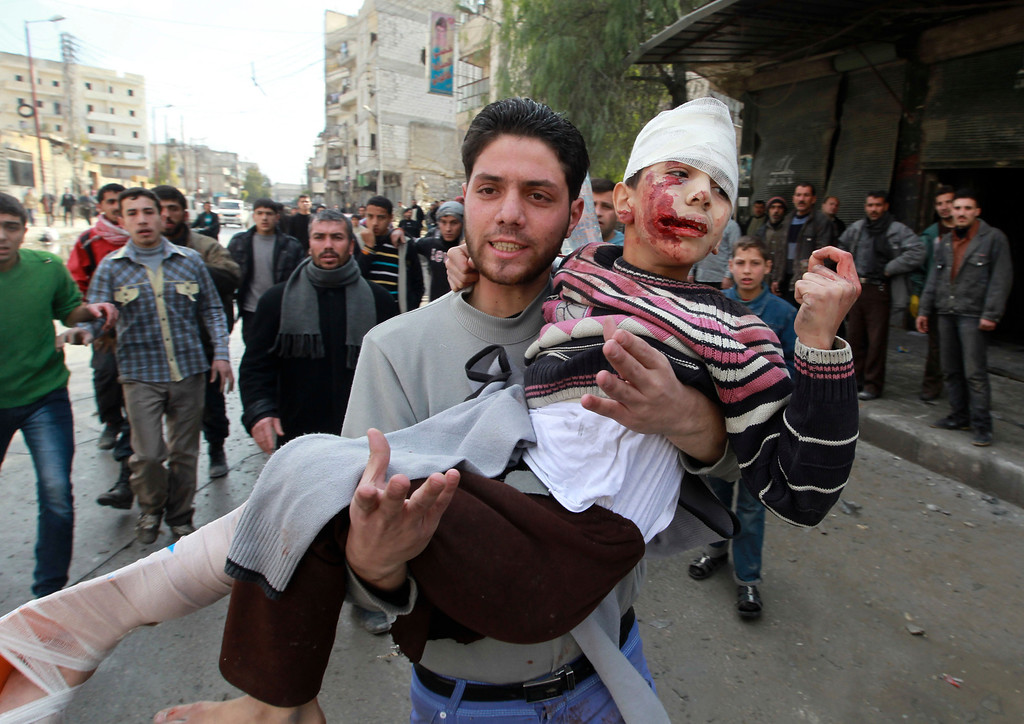 Description of . A man carries a child who was wounded after a jet missile hit the al-Myassar neighbourhood of Aleppo February 20, 2013.  REUTERS/Muzaffar Salman