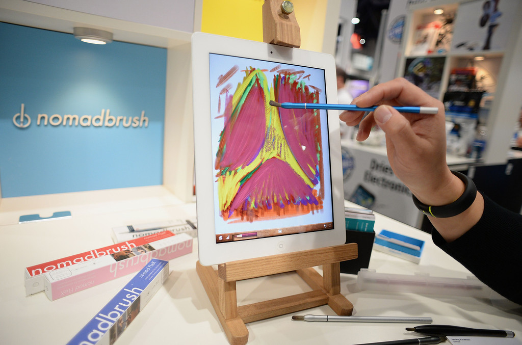 Description of . NomadBrush founder and CEO Don Lee uses a NomadBrush Flex paintbrush stylus and an oil painting app to paint on an iPad at the 2014 International CES in Las Vegas, Nevada, January 8, 2014.  Each bristle of the paintbrush stylus, which was recently released and is priced at USD $29, is conductive. AFP PHOTO / Robyn Beck/AFP/Getty Images