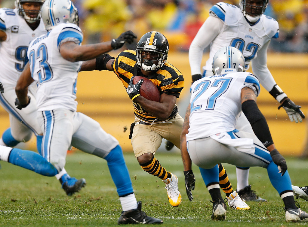 Description of . Antonio Brown #84 of the Pittsburgh Steelers looks for running room between Glover Quin #27 of the Detroit Lions and Chris Houston #23 at Heinz Field on November 17, 2013 in Pittsburgh, Pennsylvania.  (Photo by Gregory Shamus/Getty Images)