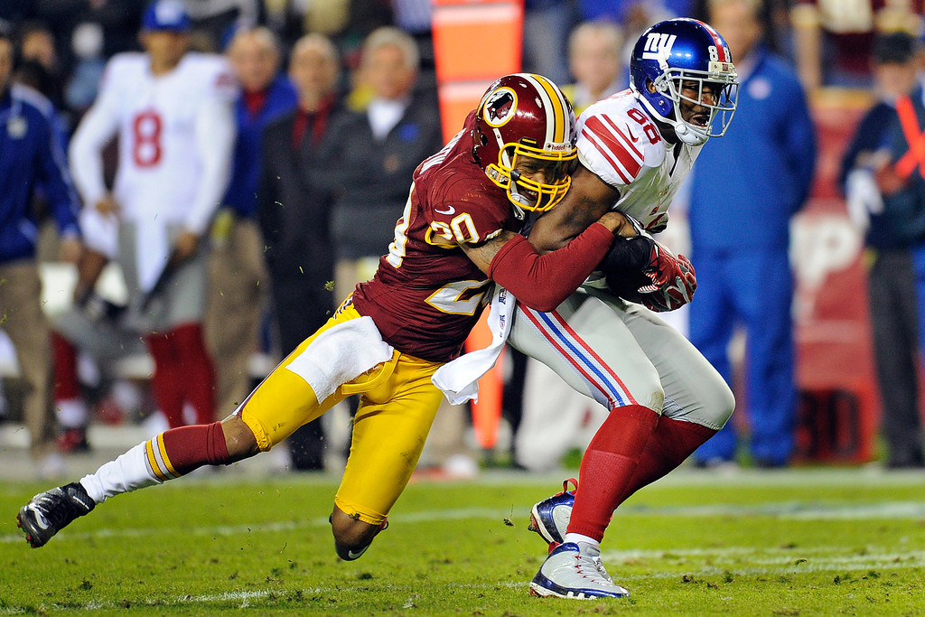 Description of . Washington Redskins defensive back Cedric Griffin (20) stops New York Giants wide receiver Hakeem Nicks (88) during the second half of an NFL football game in Landover, Md., Monday, Dec. 3, 2012. (AP Photo/Nick Wass)
