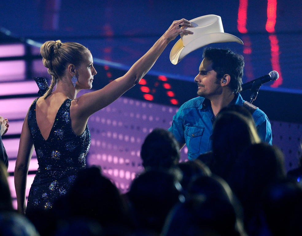 Description of . Heidi Klum, left, takes Brad Paisley's hat as he performs ìThe Mona Lisaî on stage at the 40th annual People's Choice Awards at the Nokia Theatre L.A. Live on Wednesday, Jan. 8, 2014, in Los Angeles. (Photo by Chris Pizzello/Invision/AP)