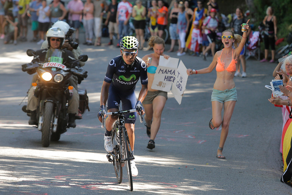 ". Two spectators with a sign in Dutch reading ""Mama it is good here\"" frun after Nairo Alexander Quintana of Colombia as he climbs towards Ax 3 Domaines during the eight stage of the Tour de France cycling race over 195 kilometers (122 miles) with start in Castres and finish in Ax 3 Domaines, Pyrenees region, France, Saturday July 6 2013. (AP Photo/Laurent Cipriani)"
