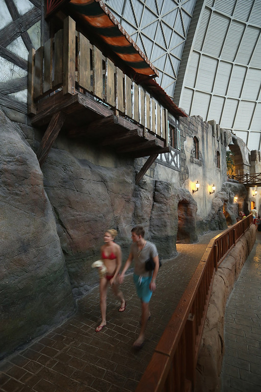 "Description of . Visitors walk past the ""Alcantara Canyon\"" that includes lockers and rooms for overnight guests at the Tropical Islands indoor resort on February 15, 2013 in Krausnick, Germany. Located on the site of a former Soviet military air base, the resort occupies a hangar built originally to house airships designed to haul long-distance cargo. Tropical Islands opened to the public in 2004 and offers visitors a tropical getaway complete with exotic flora and fauna, a beach, lagoon, restaurants, water slide, evening shows, sauna, adventure park and overnights stays ranging from rudimentary to luxury. The hangar, which is 360 metres long, 210 metres wide and 107 metres high, is tall enough to enclose the Statue of Liberty.  (Photo by Sean Gallup/Getty Images)"