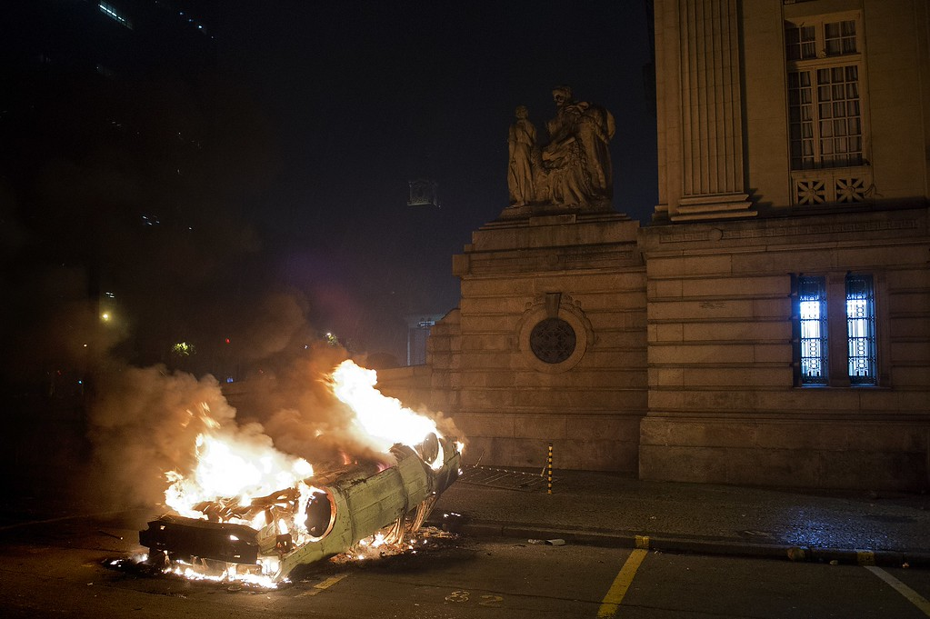 Description of . A car set on fire by demonstrators burns in front of the state Legislative Assembly (ALERJ) building in Rio de Janeiro downtown, during a protest on June 17, 2013. Tens of thousands of people took to the streets of major Brazilian cities protesting the billions of dollars spent on the Confederations Cup --and preparations for the upcoming World Cup-- and against the hike in mass transit fares.    PABLO PORCIUNCULA/AFP/Getty Images