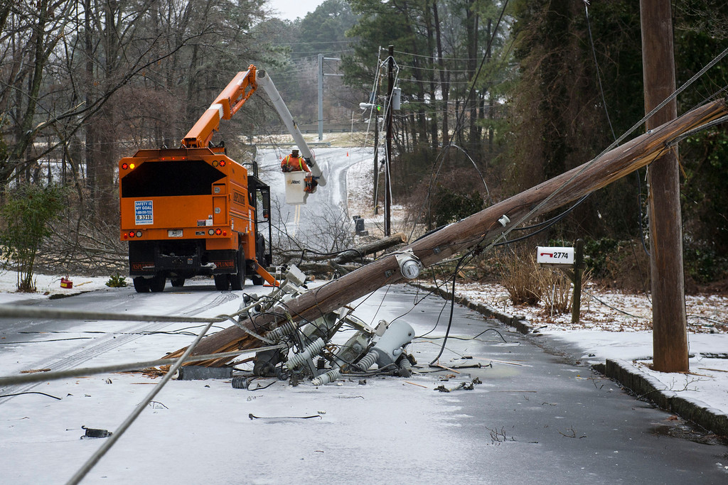 Description of . Workers remove trees and snapped power poles brought down in the road during a winter storm on Wednesday, Feb. 12, 2014, in Doraville, Ga.  Georgia utility companies report that nearly 200,000 customers were without power as ice coated trees and branches are bringing power lines down across the state.(AP Photo/John Amis)