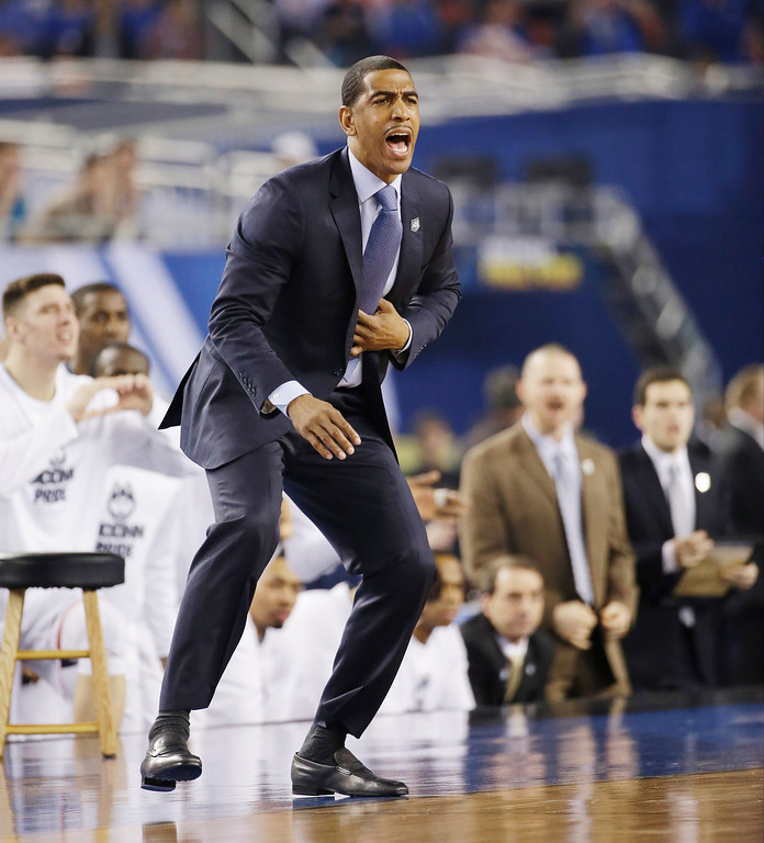 Description of . Connecticut head coach Kevin Ollie directs action from the sideline against Kentucky during the first half of the NCAA Final Four tournament college basketball championship game Monday, April 7, 2014, in Arlington, Texas. (AP Photo/David J. Phillip)