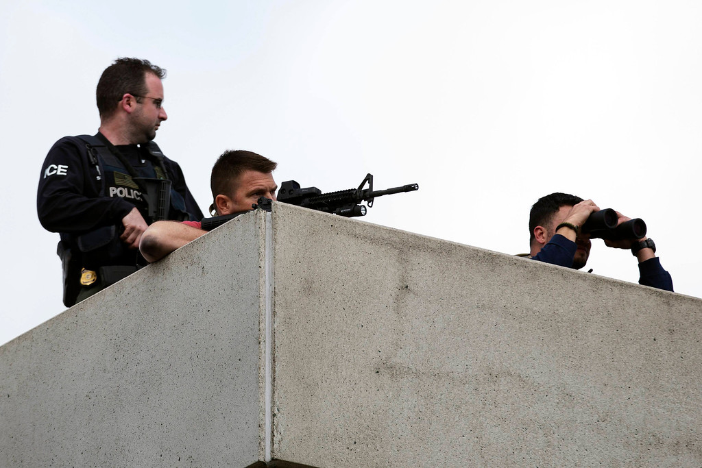 Description of . Law enforcement officers place themselves in an overhead position on Arsenal St, in the search area for Dzhokar Tsarnaev, the one remaining suspect in the Boston Marathon bombing, in Watertown, Massachusetts April 19, 2013. REUTERS/Lucas Jackson