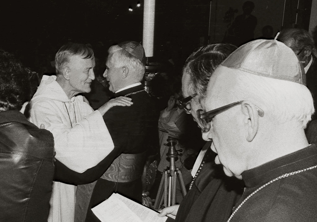Description of . Cardinal Joseph Ratzinger (C) hugs the founder of the ecumenical Taize community Brother Roger in Munich, 18 November 1978. KNA/AFP/Getty Images