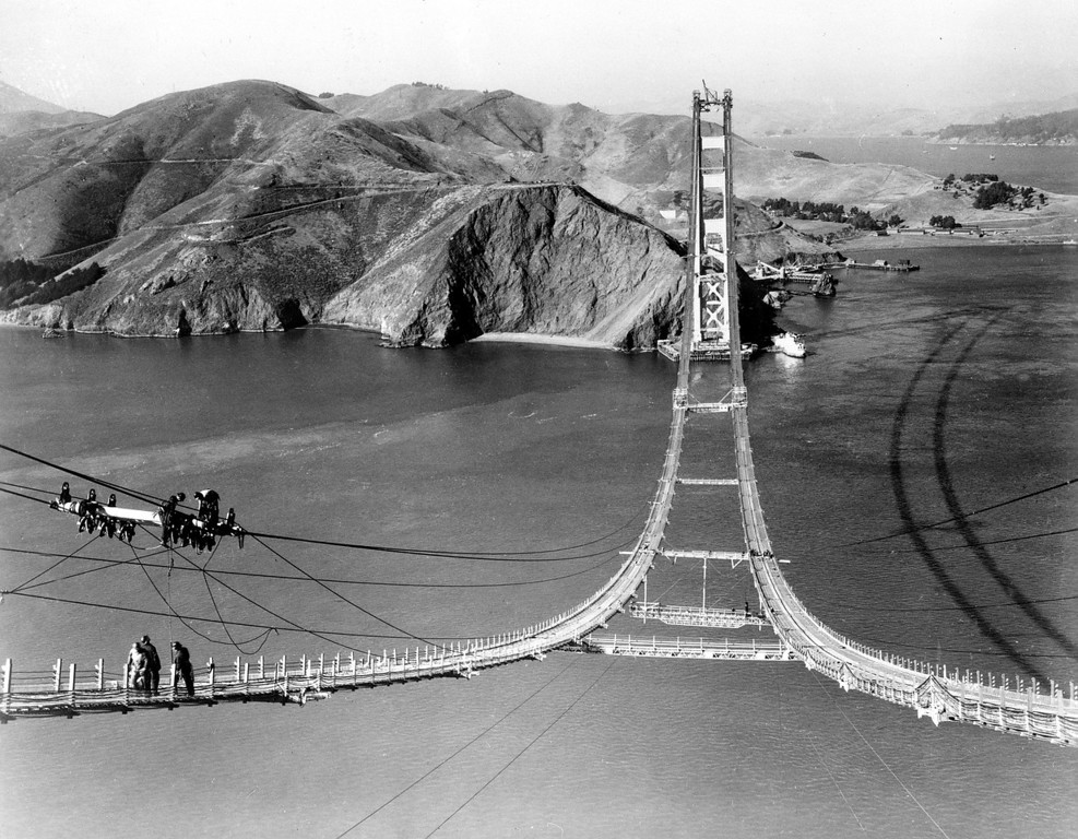 Description of . Workers complete the catwalks for the Golden Gate Bridge, spanning the Golden Gate Strait, prior to spinning the bridge cables during construction in San Francisco, Ca., Oct. 25, 1935.  (AP Photo)