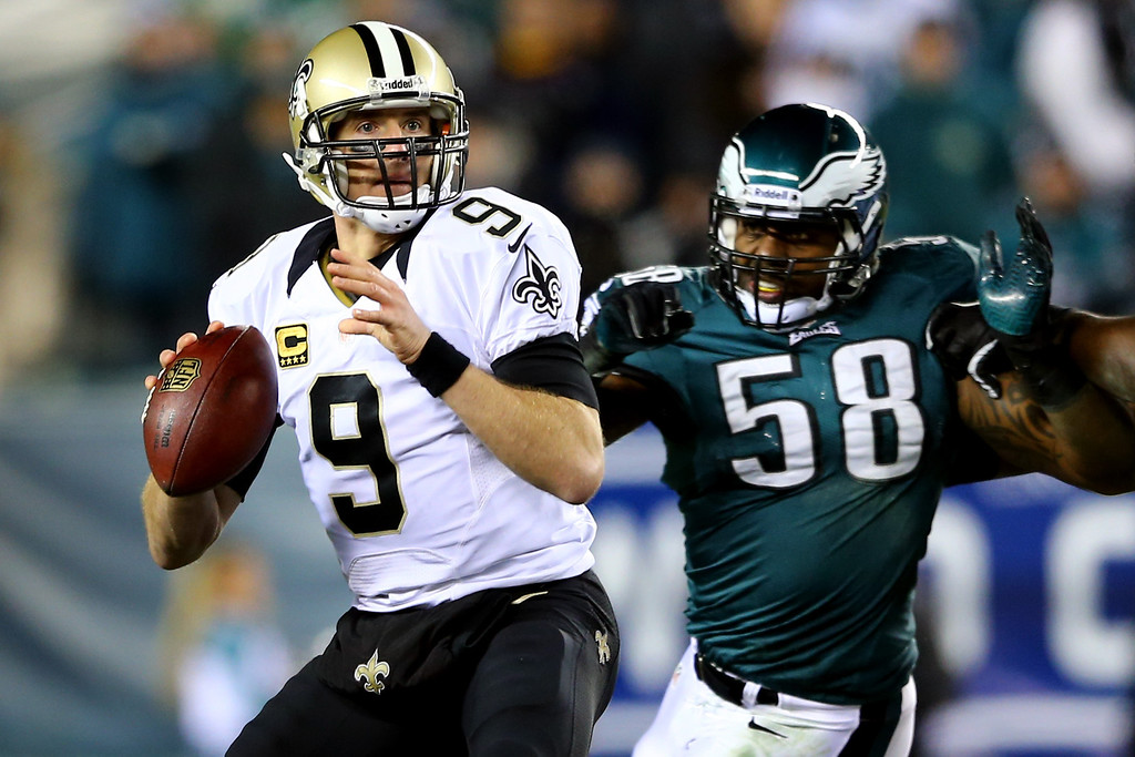 Description of . PHILADELPHIA, PA - JANUARY 04:  Drew Brees #9 of the New Orleans Saints looks to throw a pass in the first quarter against Trent Cole #58 of the Philadelphia Eagles during their NFC Wild Card Playoff game at Lincoln Financial Field on January 4, 2014 in Philadelphia, Pennsylvania.  (Photo by Elsa/Getty Images)