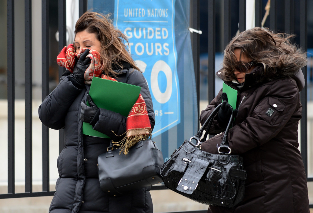Description of . Two women brace themselves against the wind as they walk past the United Nations entrance on First Avenue March 6, 2013 in New York as a winter storm heads to the eastern US. AFP PHOTO/Stan HONDA/AFP/Getty Images