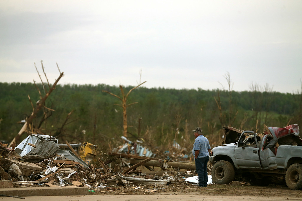Description of . A passerby stops to look at damage caused by a tornado on Sunday evening, on April 29, 2014 in Vilonia, Arkansas. After deadly tornadoes ripped through the region leaving more than a dozen dead, Mississippi, Arkansas, Texas, Louisiana and Tennessee are all under watch as multiple storms are expected over the next few days.  (Photo by Mark Wilson/Getty Images)