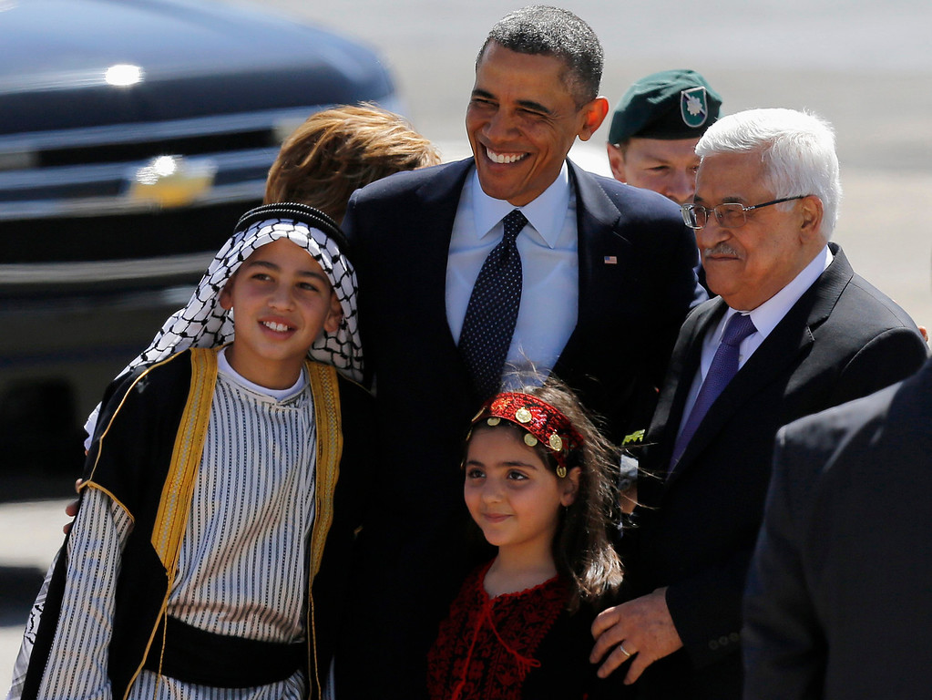 Description of . U.S. President Barack Obama (C) and Palestinian President Mahmoud Abbas (R) pose for a photo with Palestinian children during a welcoming ceremony in the West Bank city of Ramallah March 21, 2013. Taking a diplomatic detour from his first official visit to Israel, Obama traveled to the West Bank on Thursday for talks with Palestinian leaders who accuse him of letting Israel ride rough-shod over their dream of statehood. REUTERS/Ammar Awad