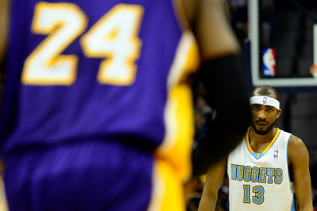 Description of . Denver Nuggets small forward Corey Brewer (13) stares down Los Angeles Lakers shooting guard Kobe Bryant (24) during the first half at the Pepsi Center on Wednesday, December 26, 2012. AAron Ontiveroz, The Denver Post