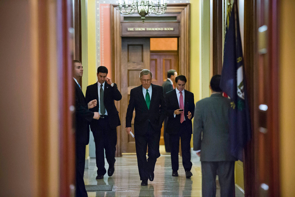 Description of . Senate Minority Leader Mitch McConnell, center, from Kentucky, departs the Strom Thurmond room after a Senate Republican caucus meeting about the fiscal cliff, on Capitol Hill on Monday, Dec. 31, 2012 in Washington. (AP Photo/Alex Brandon)