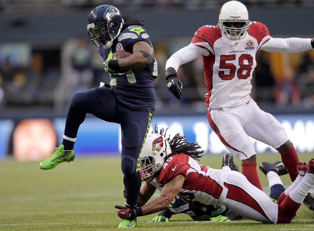 Description of . Seattle Seahawks running back Marshawn Lynch (24) runs for a 33-yard touchdown past Arizona Cardinals strong safety Rashad Johnson (49) and inside linebacker Daryl Washington (58) during the third quarterof an NFL football game in Seattle, Sunday, Dec. 9, 2012. (AP Photo/Stephen Brashear)