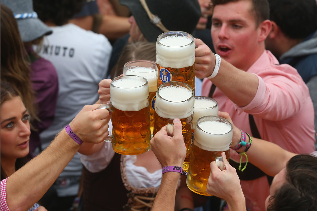 Description of . Revellers enjoy the first beer at the opening day of the Oktoberfest at Hofbraeu tent on September 21, 2013 in Munich, Germany. The Munich Oktoberfest, which this year will run from September 21 through October 6, is the world's largest beer fest and draws millions of visitors.  (Photo by Alexander Hassenstein/Getty Images)