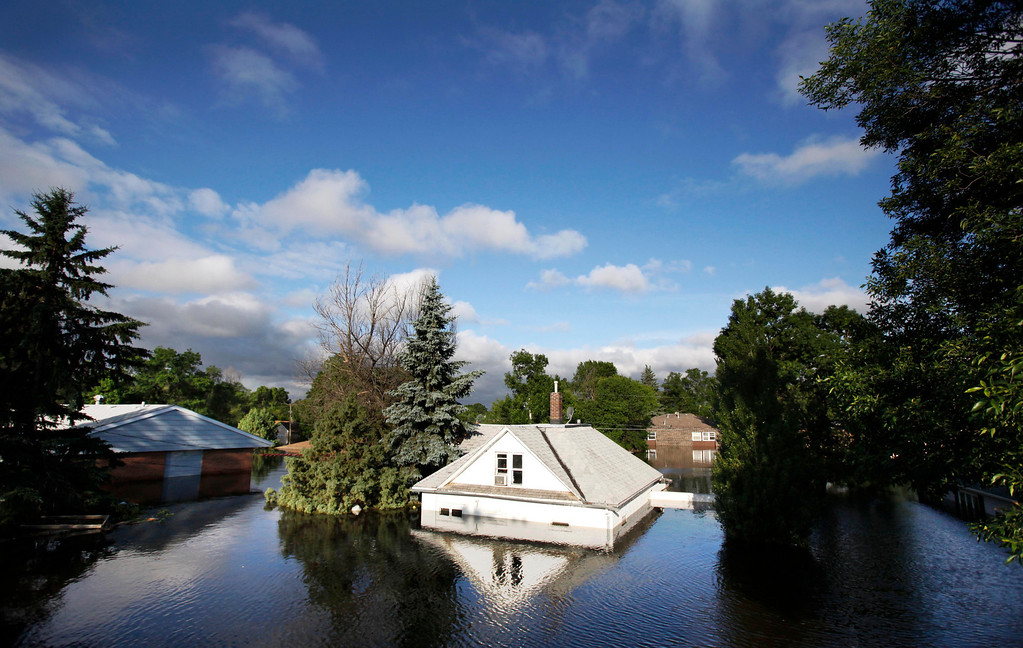 Description of . In this June 27, 2011 file photo, floodwaters from the Souris River surround homes near Minot State University in Minot, N.D. (AP Photo/Charles Rex Arbogast)