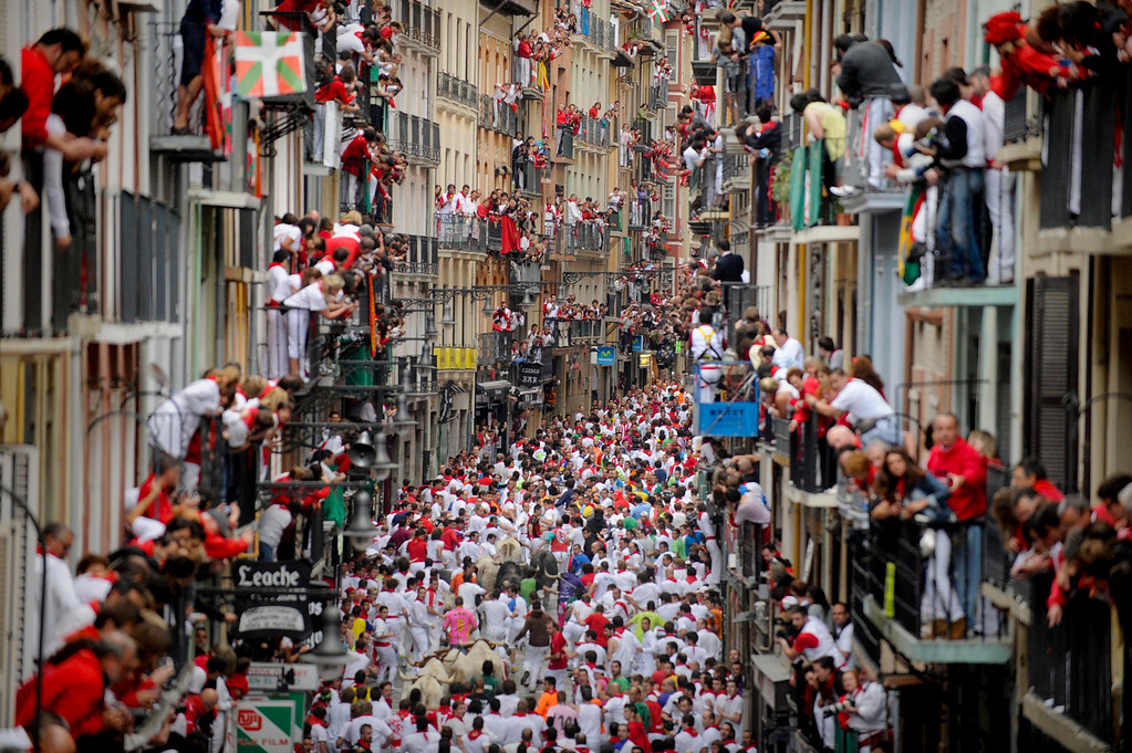 Description of . Participants run in front of Fuente Ymbro's bulls during the fifth San Fermin Festival bull run, on July 11, 2012, in Pamplona, northern Spain. The festival is a symbol of Spanish culture that attracts thousands of tourists to watch the bull runs despite heavy condemnation from animal rights groups. (PEDRO ARMESTRE/AFP/GettyImages)
