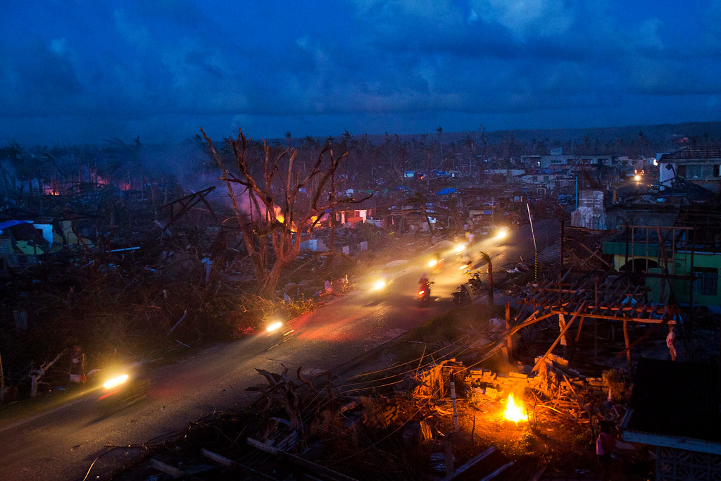 Description of . Typhoon Haiyan survivors ride motorbikes through the ruins of the destroyed town of Guiuan, Philippines on Thursday, Nov. 14, 2013.   (AP Photo/David Guttenfelder)