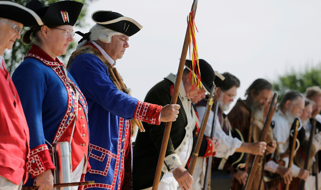 Description of . Drum major Ricardo Rodriguez, center, and other living history members, bow for a prayer during a Fourth of July Patriotic Ceremony at Fort Sam Houston National Cemetery, Thursday, July 4, 2013, in San Antonio. (AP Photo/Eric Gay)