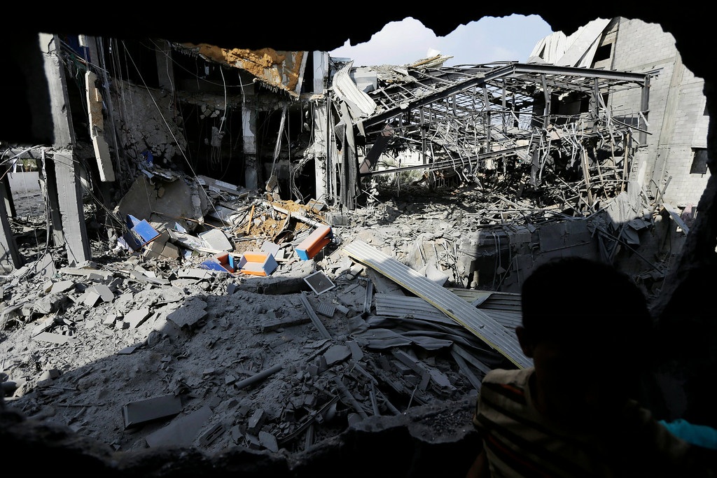 Description of . A Palestinian from a neighboring apartment building inspects the damage of the offices of the Hamas movement's Al-Aqsa satellite TV station, in Gaza City, northern Gaza Strip, destroyed by an Israeli strike, Tuesday, July 29, 2014. Early Tuesday, Israel warplanes struck a series of targets in Gaza City, including the top Hamas leader in Gaza, Ismail Haniyeh's house and government offices, while Gaza's border area with Israel was hit by heavy tank shelling. (AP Photo/Lefteris Pitarakis)