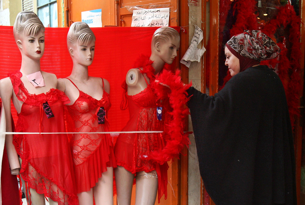 . A Palestinian woman adjusts a feathered scarf on a mannequin at a lingerie shop, decorated for Valentine\'s Day, in the West Bank city of Nablus, Thursday, Feb. 14, 2012. Valentine\'s Day is a festival of romantic love and is celebrated in many countries over the world by giving cards, flowers or gifts to spouses or partners. (AP Photo/Nasser Ishtayeh)