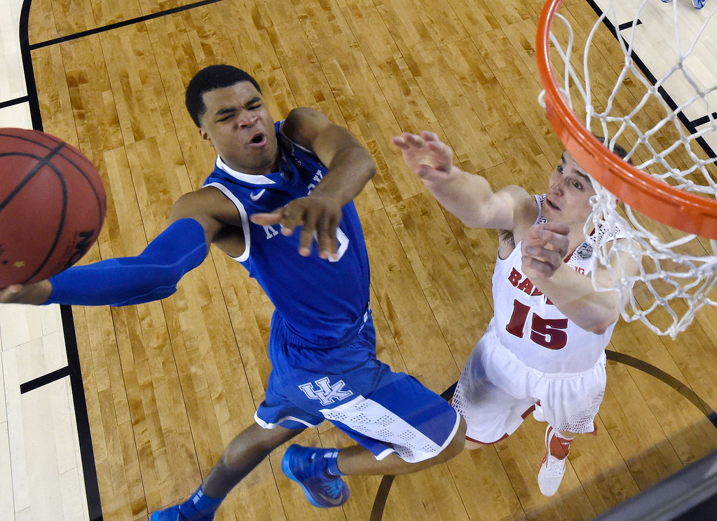 Description of . Kentucky guard Andrew Harrison (5) drives to the basket past Wisconsin forward Sam Dekker, right, during the first half of an NCAA Final Four tournament college basketball semifinal game Saturday, April 5, 2014, in Arlington, Texas. (AP Photo/Chris Steppig, pool)