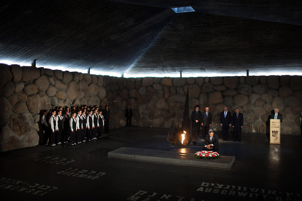 Description of . U.S. President Barack Obama pays his respects in the Hall of Remembrance in front of Israel's President Shimon Peres, Israel's Prime Minster Benjamin Netanyahu, Chairman of the Yad Vashem Directorate Avner Shalev, Rabbi Yisrael Meir Lau and the Abnkor Children's Choir after marines layed a wreath on his behalf during his visit to the Yad Vashem on March 22, 2013 in Jerusalem, Israel. (Photo by Uriel Sinai/Getty Images)