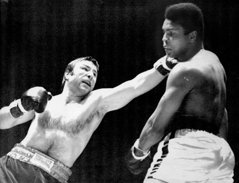 Description of . Chuvalo Scores With  A Left - George Chuvalo, Canadian heavyweight champion, connects with a left to the head of Muhammad Ali, former heavyweight champion in action in the first round of their scheduled 12-round fight at Vancouver's Pacific Coliseum Monday night. 1972. Denver Post Library photo archive