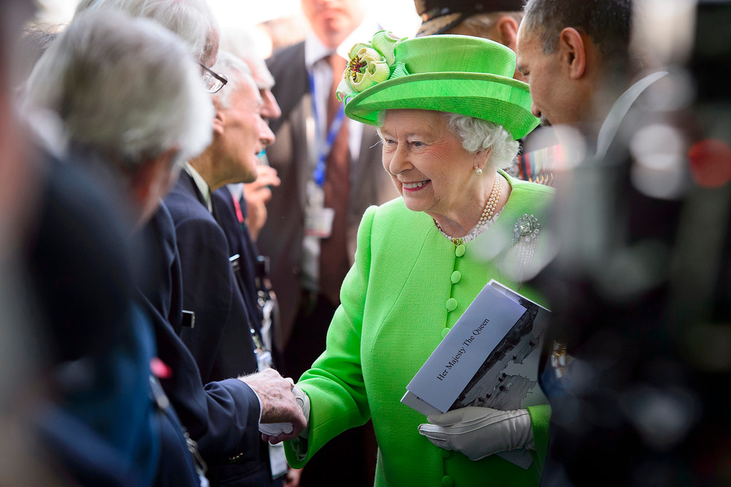 Description of . Britain's Queen Elizabeth II greets participants during a British D-Day commemoration ceremony in Bayeux cemetery, northern France, Friday, June 6, 2014. World leaders and veterans gathered by the beaches of Normandy on Friday to mark the 70th anniversary of World War Two's D-Day landings. (AP Photo/Leon Neal, Pool)