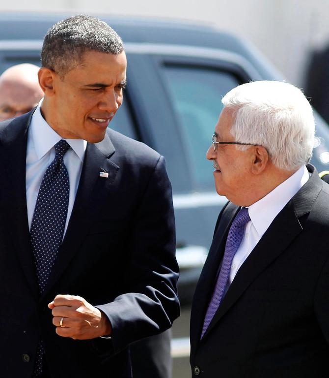 Description of . U.S. President Barack Obama gestures while walking next to Palestinian President Mahmoud Abbas (R) before reviewing troops during an arrival ceremony at the Muqata Presidential Compound in the West Bank City of Ramallah March 21, 2013.     REUTERS/Larry Downing