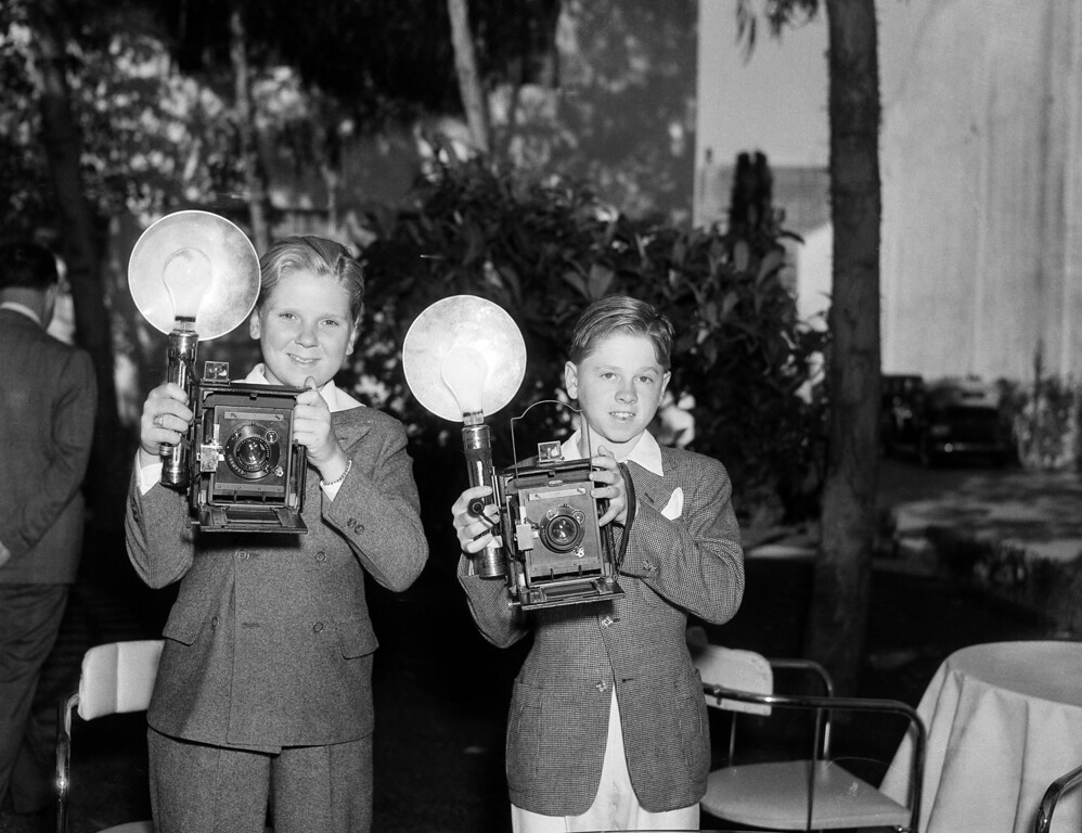 Description of . Jackie Cooper, left, and Mickey Rooney, child actors, after an opportunity to use cameras owned by visiting newspaper men, believe they'd rather work behind the lenses instead of in front of them. They are shown in their first attempt at picture taking, June 22, 1935. (AP Photo/Frank Filan)