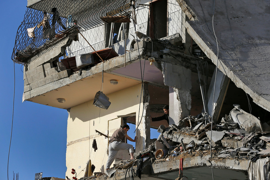 Description of . Palestinians inspect damages of the el-Yazje family apartment building which was destroyed following an overnight Israeli missile strike in Gaza City, Thursday, July 17, 2014. The Israeli military says it has struck 37 targets in Gaza ahead of a five-hour humanitarian cease-fire meant to allow civilians to stock up after 10 days of fighting. The Gaza Interior Ministry says four people were killed and that a 75-year-old woman died of wounds from the day before. The Israeli army says Hamas fired 11 rockets at Israel early Thursday. Palestinian health officials say that in total, at least 225 Palestinians have been killed. On the Israeli side, one man was killed since July 8. (AP Photo/Lefteris Pitarakis)